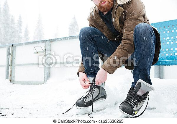 Man tying shoelace on ice skates outdoors - csp35636265