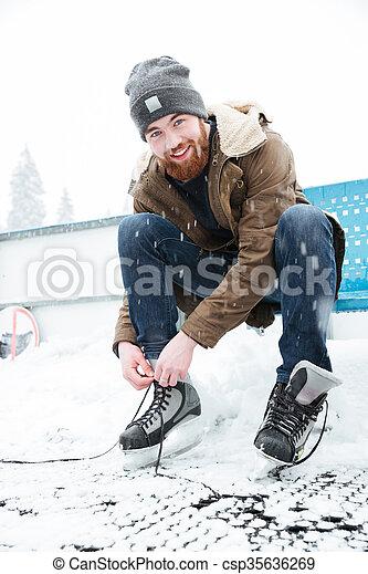 Man tying shoelace on ice skates outdoors - csp35636269