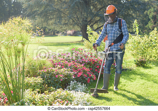 man using a grass trimmer - csp42557664
