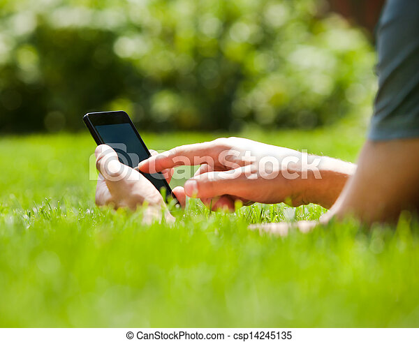 Man using mobile smart phone outdoor in summer - csp14245135