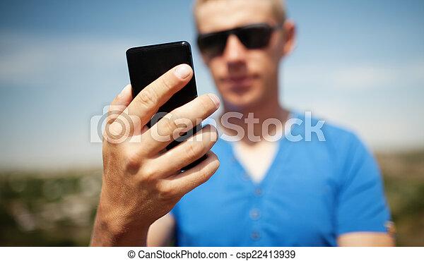 Man using mobile smart phone outdoor - csp22413939