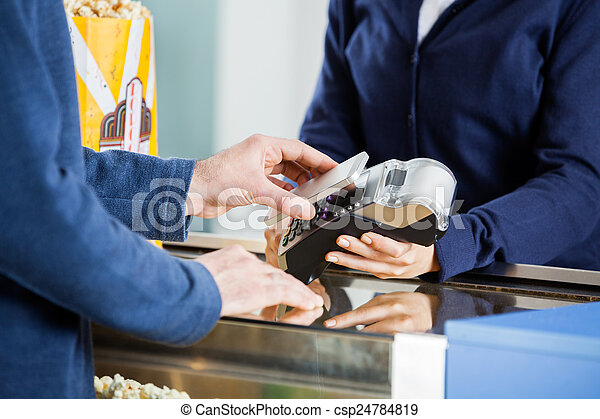 Man Using NFC Technology At Concession Counter - csp24784819