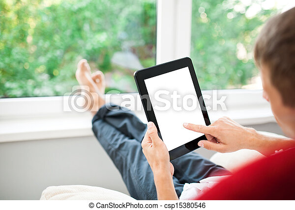 Man using tablet on sofa at home - csp15380546