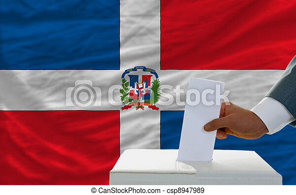man voting on elections in dominican republic in front of flag - csp8947989