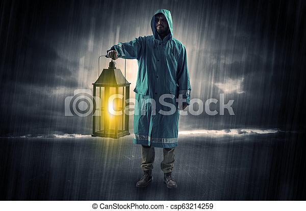 Man walking in storm with lantern - csp63214259