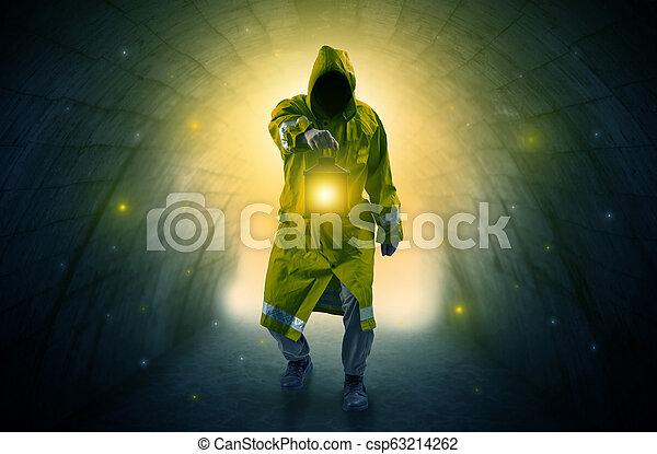Man walking with lantern in a dark tunnel - csp63214262