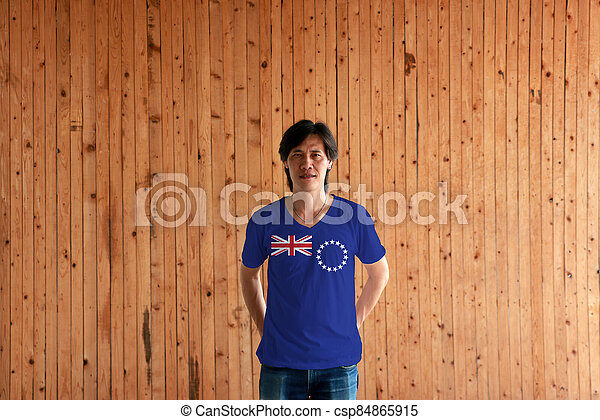 Man wearing Cook Islands flag color of shirt and standing with crossed behind the back hands on the wooden wall background. - csp84865915