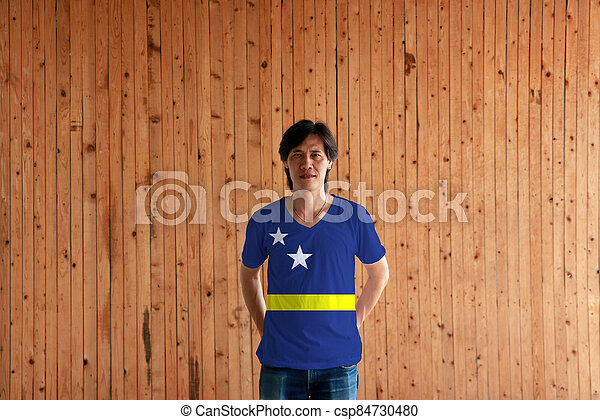 Man wearing Curacao flag color of shirt and standing with crossed behind the back hands on the wooden wall background. - csp84730480