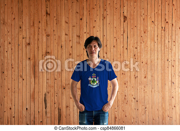 Man wearing Maine flag color shirt and standing with two hands in pant pockets on the wooden wall background. - csp84866081