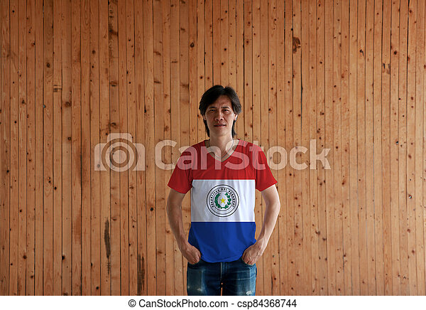 Man wearing Paraguay flag color shirt and standing with two hands in pant pockets on the wooden wall background. - csp84368744