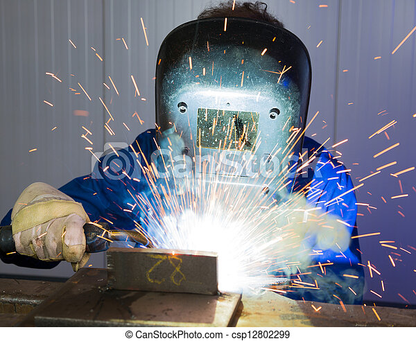 Man welding steel creating many sparks - csp12802299
