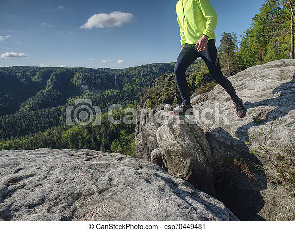 Man while jumping during a trail running in the mountains - csp70449481