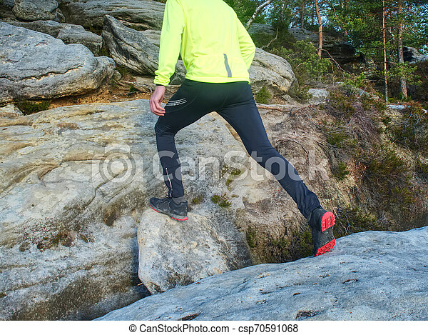 Man while jumping during a trail running in the mountains - csp70591068