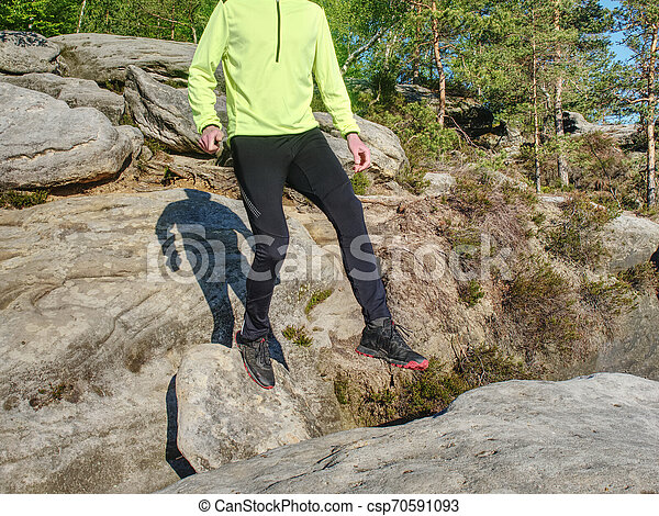 Man while jumping during a trail running in the mountains - csp70591093