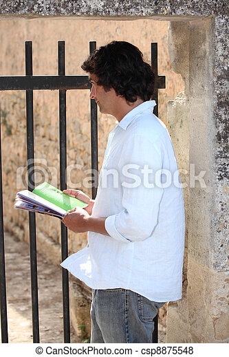 man with a guidebook watching something - csp8875548