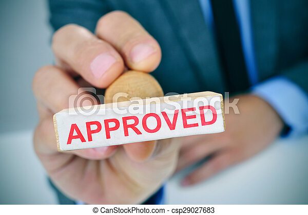 man with a rubber stamp with the word approved - csp29027683