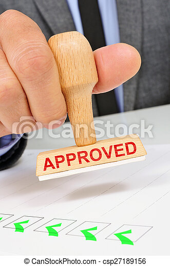 man with a rubber stamp with the word approved - csp27189156