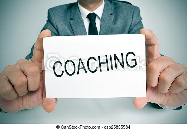 man with a signboard with the word coaching - csp25835584