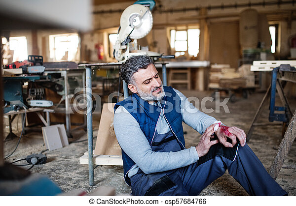 Man with an injured hand after accident at work in the carpentry workshop. - csp57684766