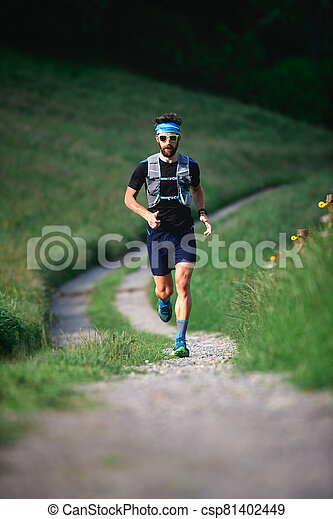 Man with beard athlete running in the mountains during a workout - csp81402449