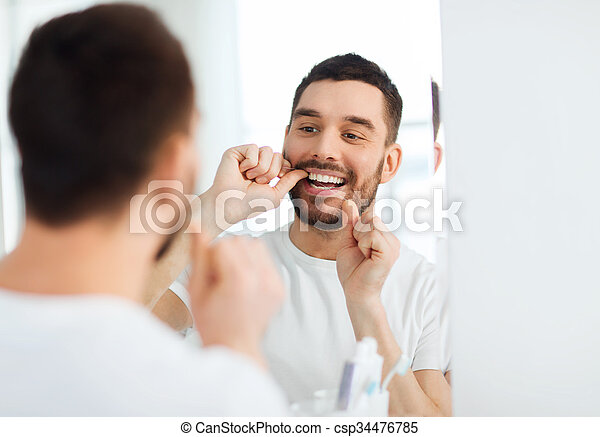 man with dental floss cleaning teeth at bathroom - csp34476785