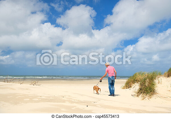 Man with dog at the beach - csp45573413