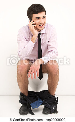 Man with mobile phone sitting on toilet. Businessman talking on phone while sitting on toilet  - csp23009022