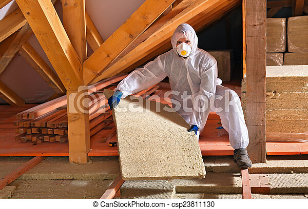 Man with rockwool panel installing insulation layer - csp23811130