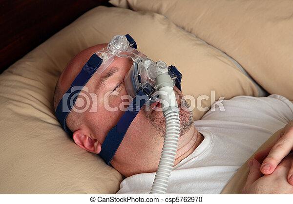 Man with sleep apnea using a CPAP machine - csp5762970