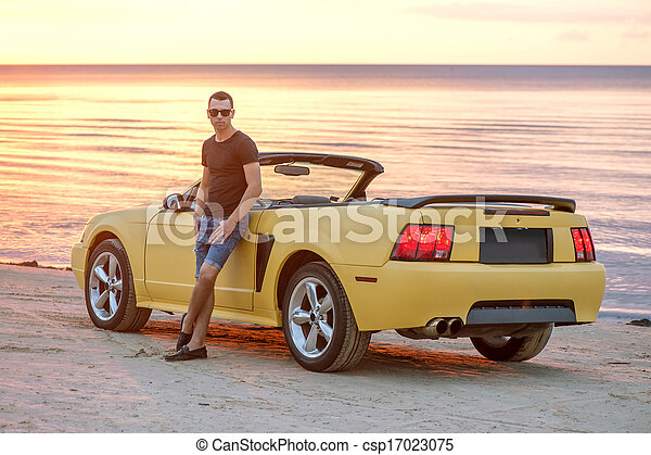 Man with super car on back of sunset - csp17023075