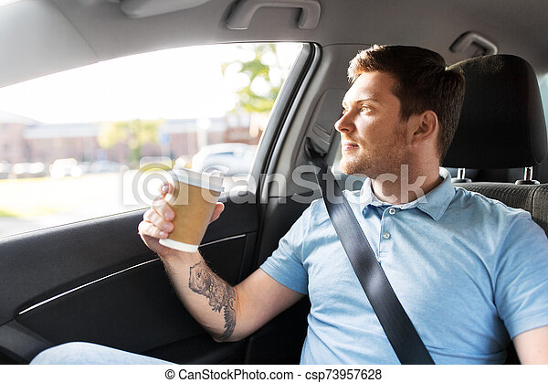 man with takeaway coffee on back seat of taxi car - csp73957628