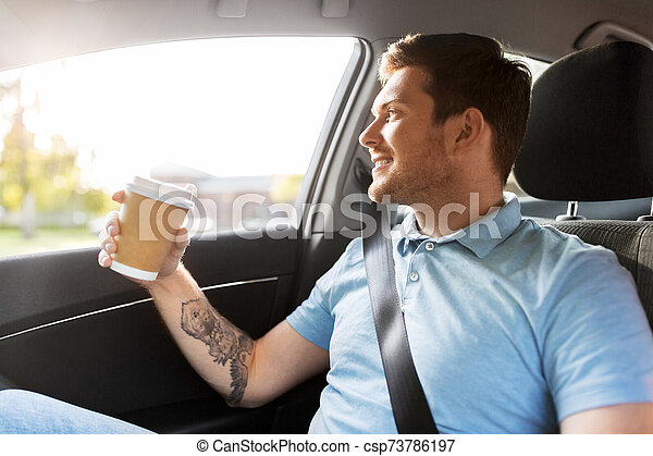 man with takeaway coffee on back seat of taxi car - csp73786197