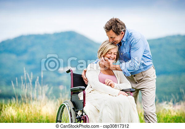 Man with woman in wheelchair - csp30817312