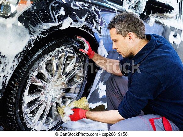 Man worker washing car's alloy wheels on a car wash  - csp26819158