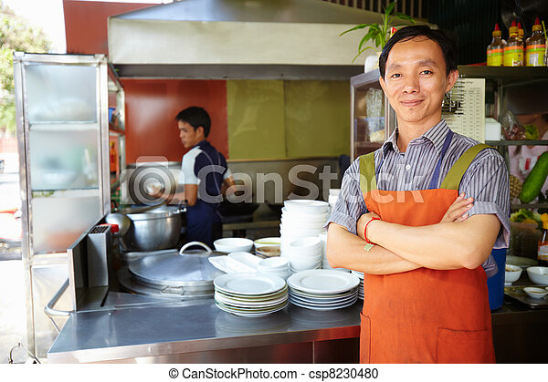 Man working as cook in Asian restaurant kitchen - csp8230480