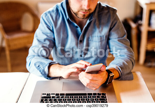 Man working from home on smart phone and laptop - csp39019279