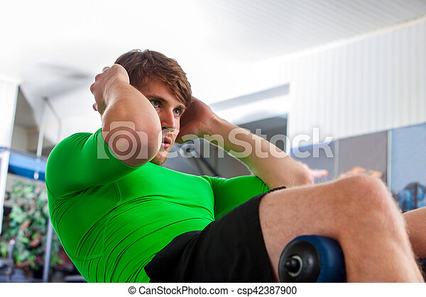 Man working his abdominal crunches with its own weight . - csp42387900