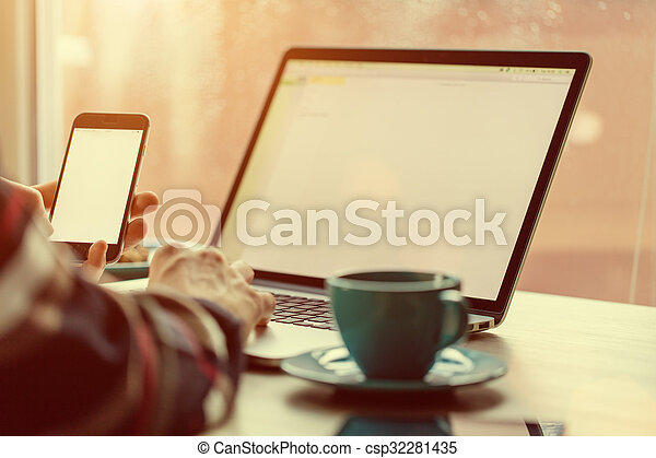 Man working on notebook, with a fresh cup of coffee. - csp32281435