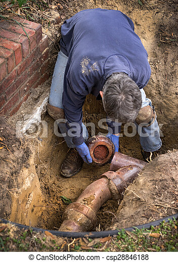 man working on old clay ceramic sewer line pipes man