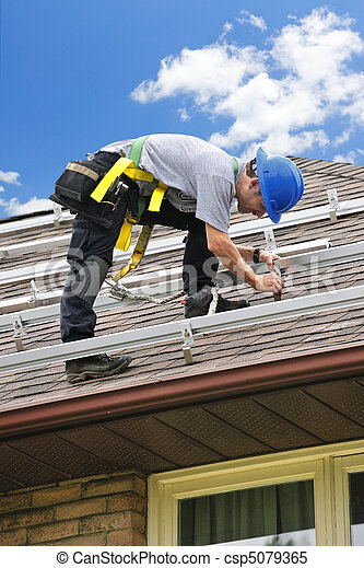 Man working on roof installing rails for solar panels - csp5079365