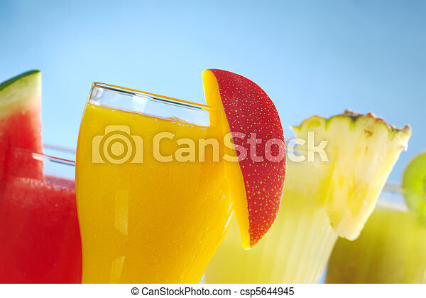 Mango, melon, pineapple and kiwi smoothies garnished with the corresponding fruit on the rim on blue background (Selective Focus, Focus on the mango smoothie in the front)  - csp5644945