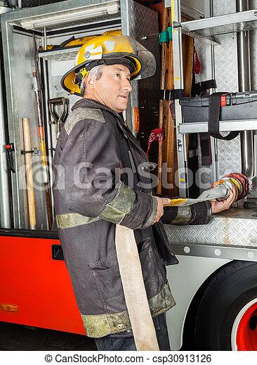 Bombero arreglando manguera de agua en el camión en la estación de bomberos - csp30913126