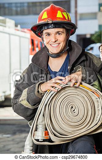 Bombero feliz sosteniendo manguera en la estación de bomberos - csp29674800