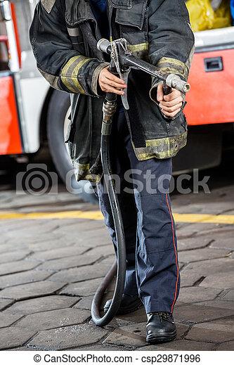 Bombero sosteniendo manguera de agua en la estación de bomberos - csp29871996