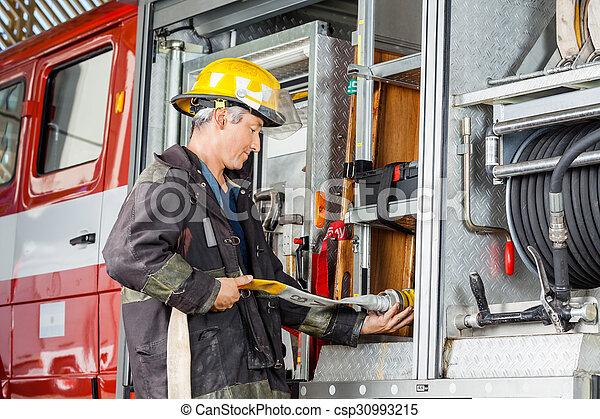 Bombero arreglando manguera de agua en un camión en la estación de bomberos - csp30993215