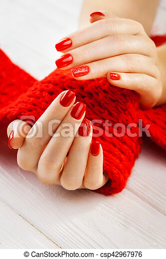 manicure with a red knitted scarf - csp42967976