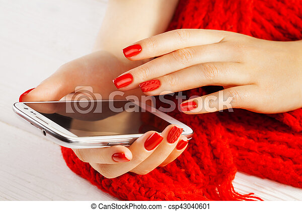 manicure with smartphone and red knitted scarf - csp43040601