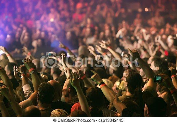 Mucha gente animando y levantando manos en un concierto de música en vivo - csp13842445