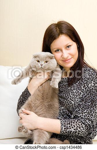 La chica tiene un gato gris en las manos - csp1434486