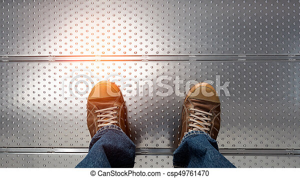 man's feet wearing jeans and leather boots - csp49761470